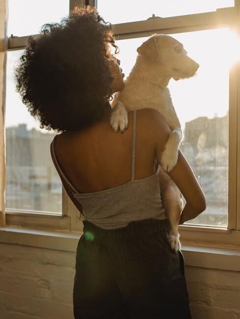 Vrouw met een hond in haar armen kijkt uit het raam