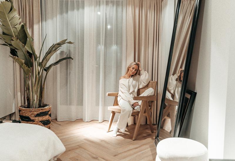 Lisanne de Bruijn in woonkamer op rotan Westwing stoel met groene grote plant voor spiegel