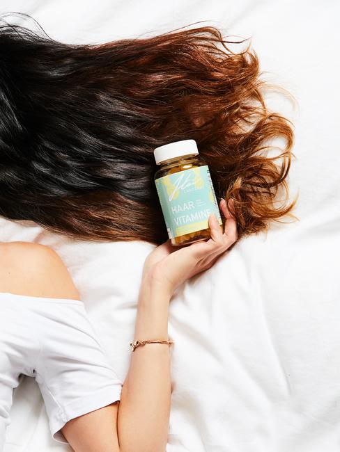 Vrouw met lang bruin haar en haarverzorgingsvitamine