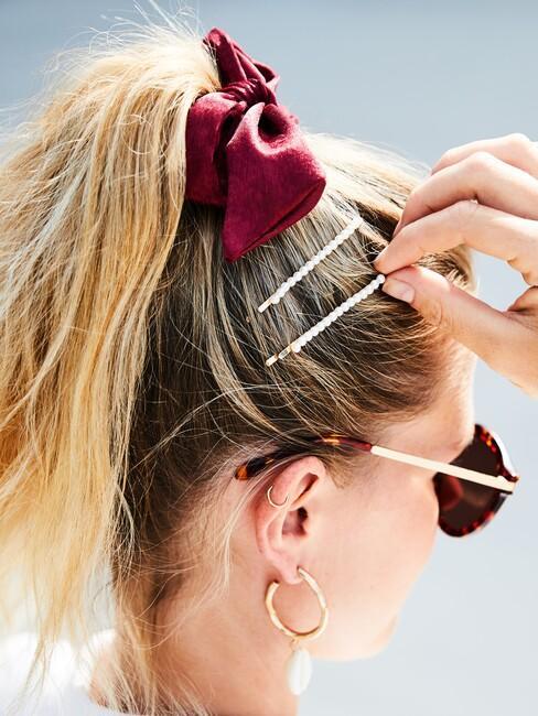 Pluizig haar in paardenstaart met scrunchie en haarklipjes