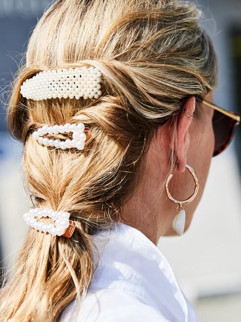 vrouw met lang blond haar in klipjes bezet met parels