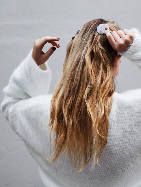 vrouw met lang blond haar en schelpklipjes