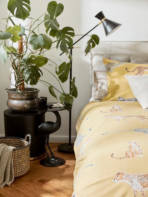 geel dekbed met zwarte lamp en plant