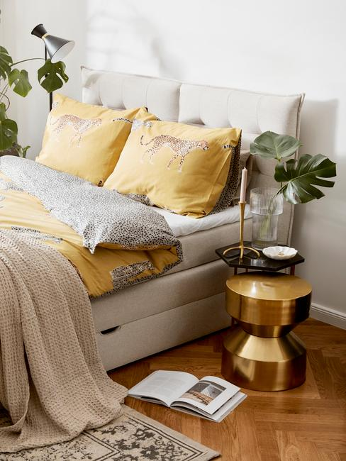 grijze boxspring met gouden tafel en geel dekbed