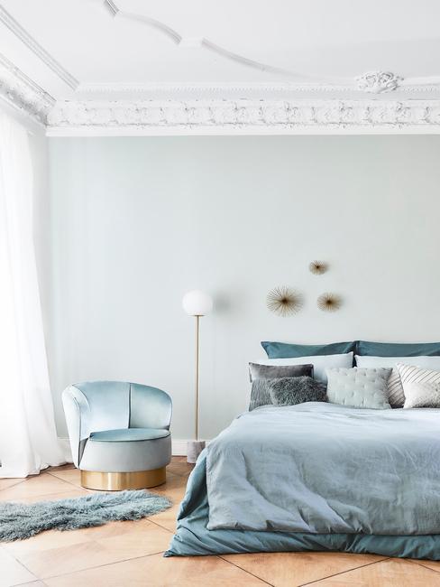 Blauwe slaapkamer met blauw bed en gouden wand deco