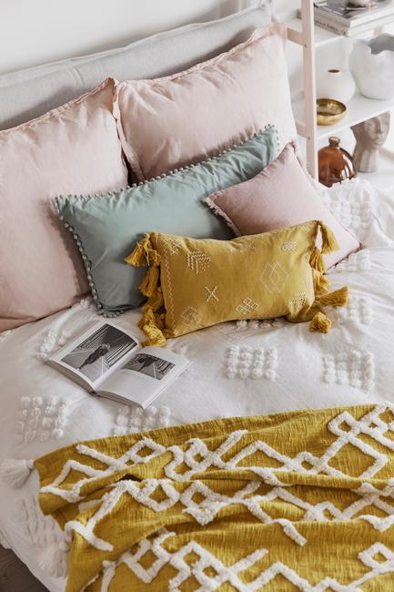 Wit dekbed met roze, gele en groene kussens