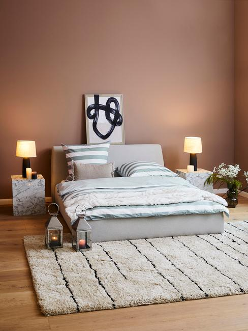 aarde kleur muur met een grijs bed wit kleed en marmere tafel