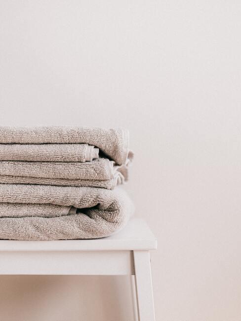 handdoeken wassen: handdoeken in beige op houten kruk