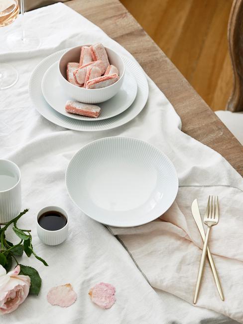 Een wit tafelkleed met wit serviesgoed en bestekset in goud kleur