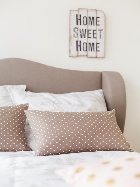 Beige kussens op groot bed