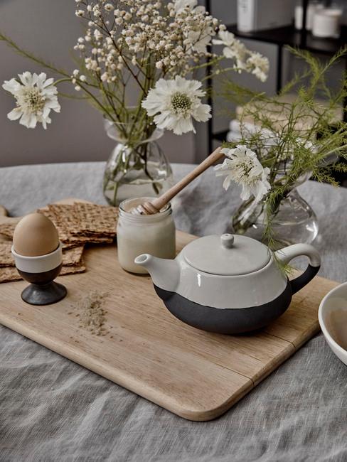 Houten dienblad en serviesgoed in wit en grijs en bloemen in vaas