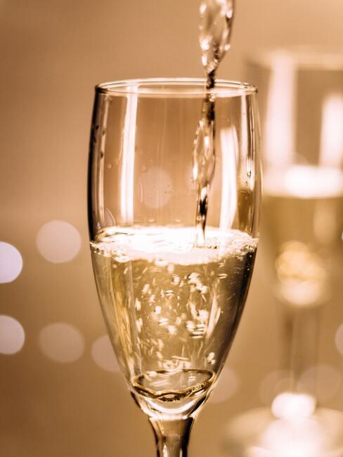 De vrouw schenkt champagne in champagneglas