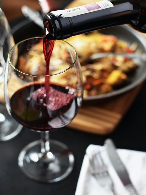 Rode wijnglas naast een houten dienblad