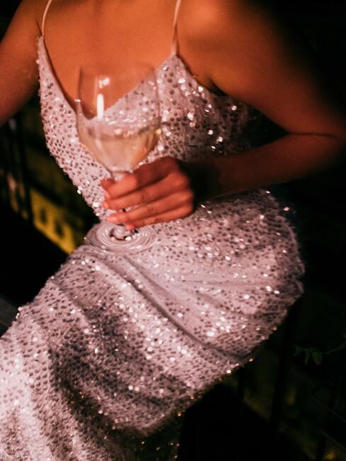 Een vrouw in een glimmende zilveren jurk