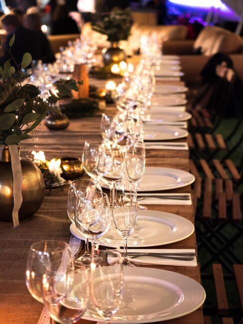 Witte serviesgoed op houten tafel en wijnglazen naast kaarsen