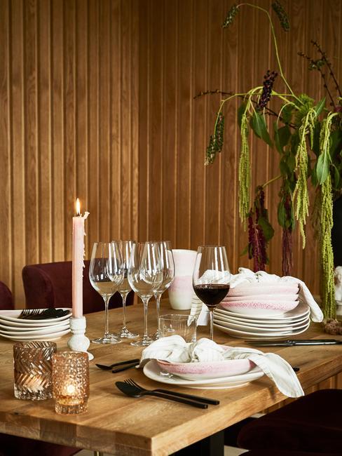 eten met vrienden : witte serviesgoed op houten tafel en wijnglazen naast kaarsen