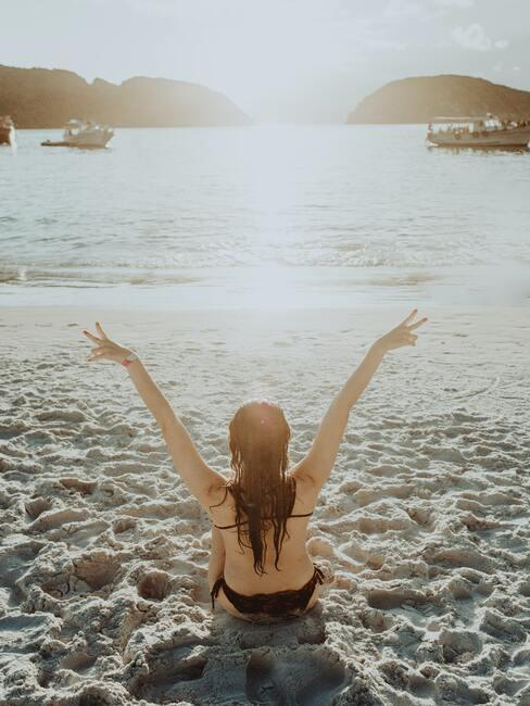 De vrouw ligt te zonnen op het strand