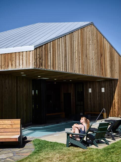 Ligstoelen in de tuin van een groot houten huis