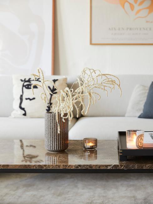Witte zitbank naast salontafel met vaas