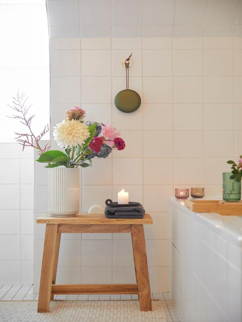 Witte vaas met bloemen op de houten kruk