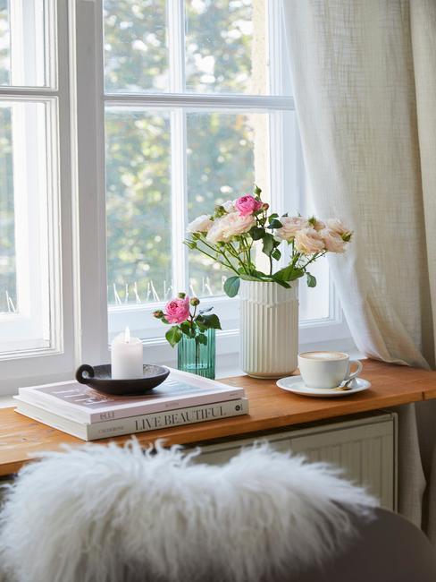 Witte vaas met bloemen op de vensterbank