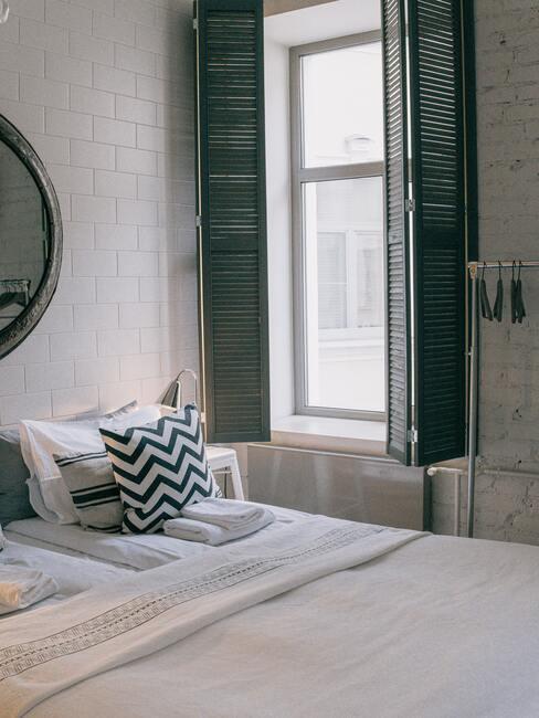 Slaapkamer met witte bedlinnen en zwarte sierkussens