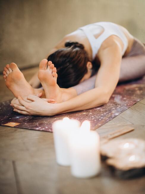 De vrouw doet thuis yoga in de woonkamer