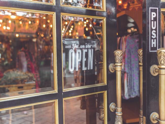 Close-up lokale kledingwinkel met bordje Open aan de deur