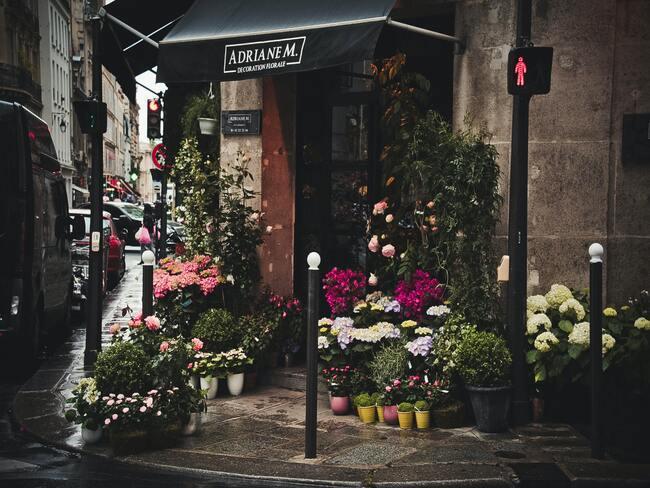 Bloemenwinkel met uitgestalde bloemen op hoek van straat - support your locals