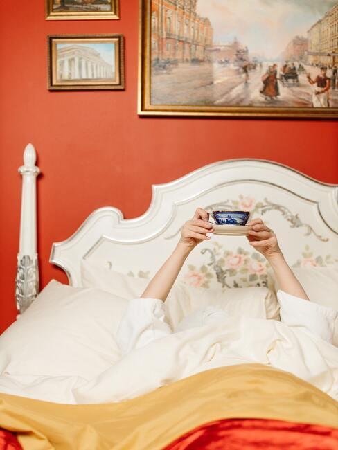 Wit hemelbed met vrouwenhanden die een kopje thee ophoog houden op oranje achtergrond met schilderijen