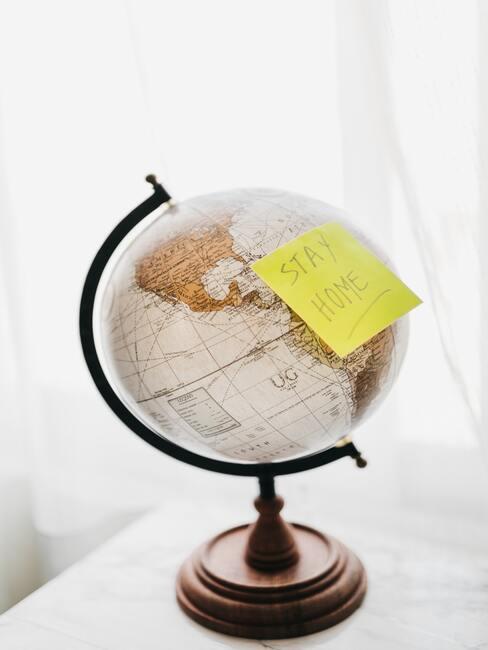 """wereldbl op witte tafel met gele sticker """"stay home"""" - Staycation"""