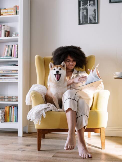 Vrouw en hond in gele fauteuil met tijdschrift op witte achtergrind met wit boekenrek