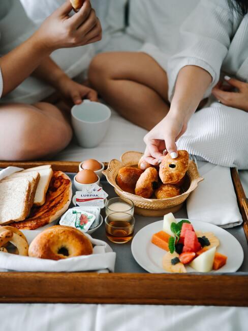 close-up ontbijt op bed met fruit, eitjes, brood en koffiekoeken met twee personen op de achtergrond
