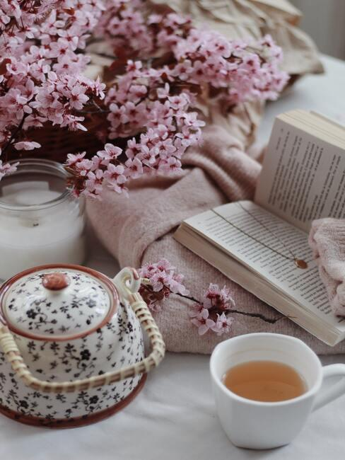 Roze bloemen, witte kaars, theepot en kopje met thee, boek en deken in beigetinten - Staycation