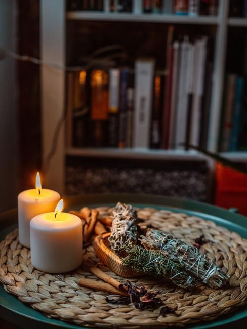 Close-up kaarsen, houten scheplelep en rookbundels op rieten placemat met boeken op de ahctergrond