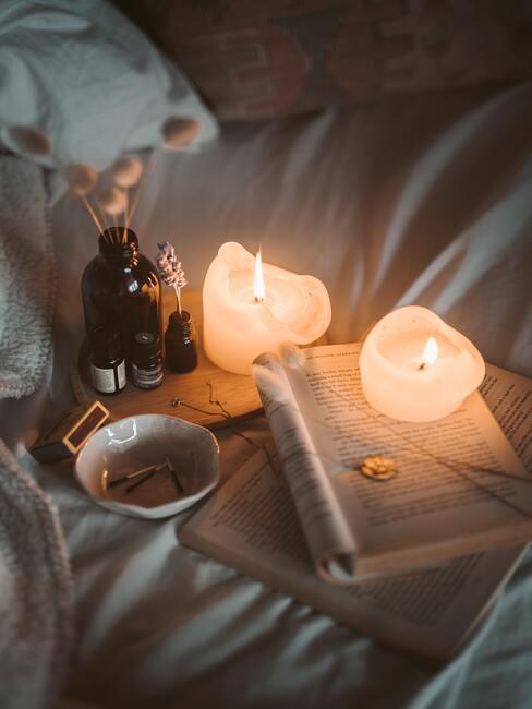 boek emt kaarsen en flesjes etherische olie op bed - Zelf luchtverfrisser maken