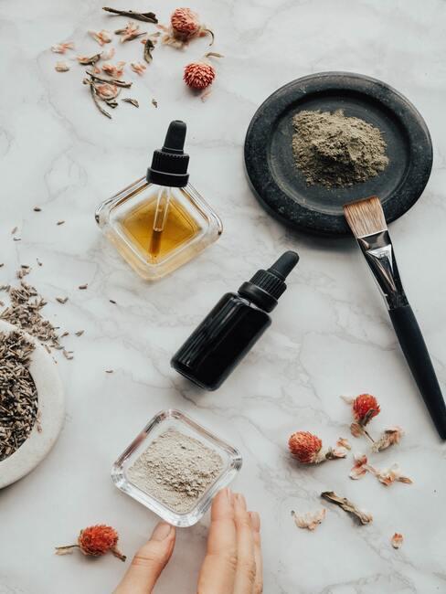etherische olie, lavendel, pensel, gedrooogde bloemen en parfum op marmeren achtergrond