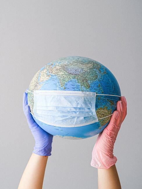 Een wereldbol in de handen van een vrouw die wegwerphandschoenen draagt