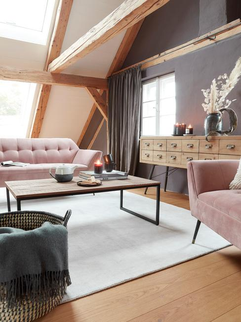 Grote woonkamer met roze zitbank en vloerkleed in wit