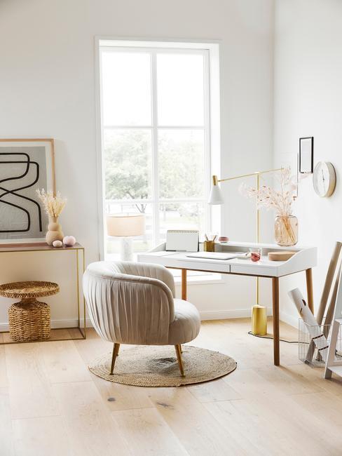 Woonkamer in wit met goudkleurige tinten en zachte fauteuil