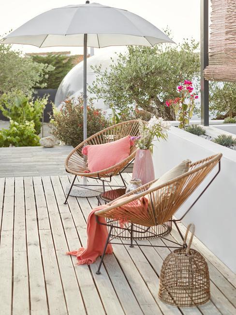 houten stoelen met roze kussens en witte parrasol