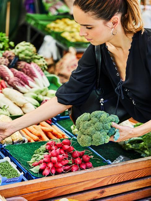 Vrouw op de markt kiest groente uit