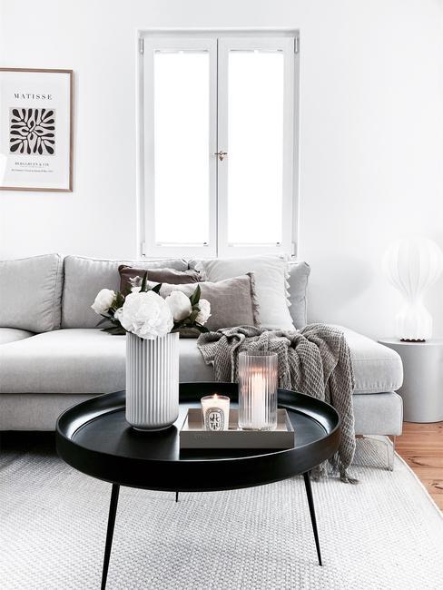 Fluwelen zitbank in grijs met zachte sierkussens en salontafel in zwart