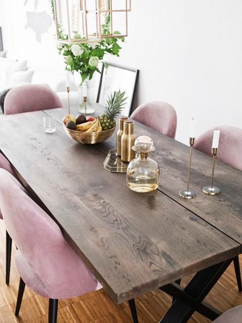 Woonkamer in witte en roze tinten met fluwelen stoelen in roze en massief houten tafel