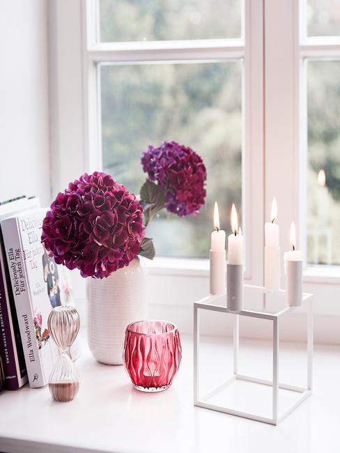 Horoscoop schorpioen: bloemen in paars in vaas in wit naast kaarshouder