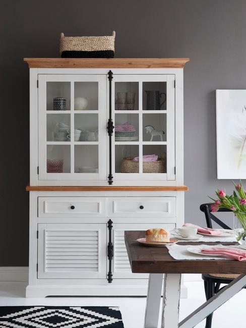 Vitrinekast in de woonkamer naast een houten tafel