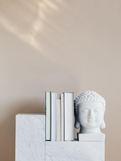 Decoratief object Buddha op wit dressoir naast boeken