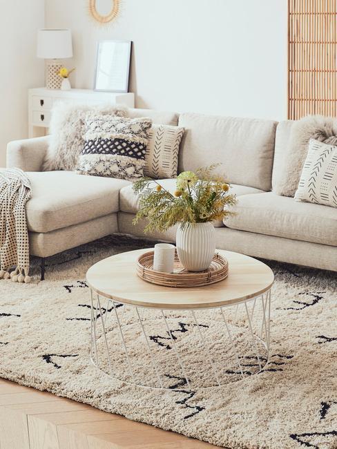 Horoscoop Boogschutter: comfortabele beige bank met sierkussens naast een houten salontafel met kaarsen