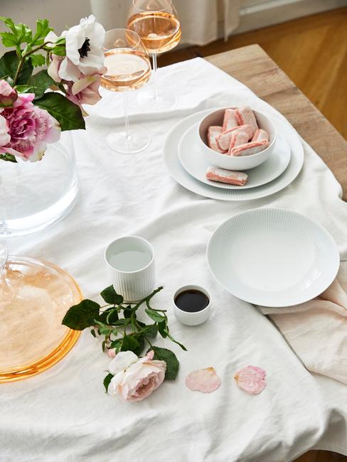 Gedekte tafel met veel kaarsen en bloemen als tafeldecoratie