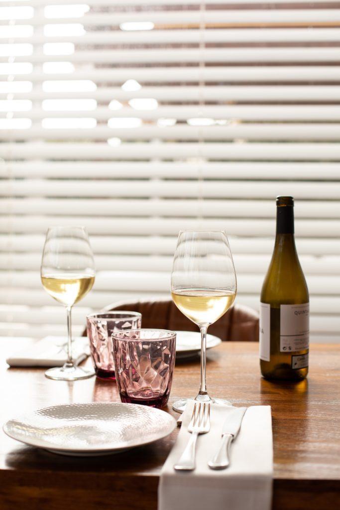 2 glazen wij op een gedekte tafel met wit servies